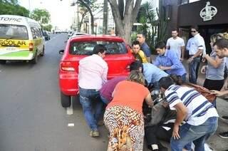 Populares retiram homem debaixo de carro na Avenida Afonso Pena (Foto: João Garrigó)