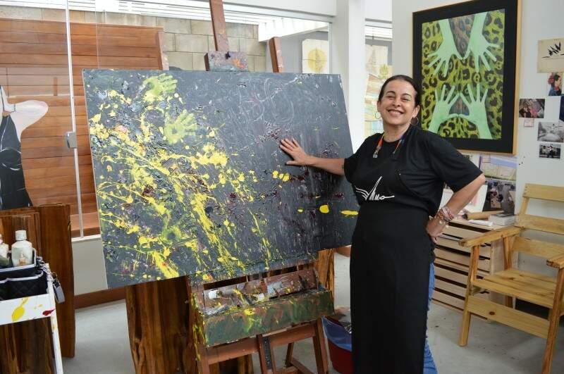 Lúcia ao lado da primeira tela que pintou dentro do Multiplo Ateliê. (Foto: Thailla Torres)