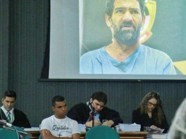 Claudinei e Nando, que aparece na foto no telão, estão sendo julgados nesta sexta-feira. (Foto: Marina Pacheco)