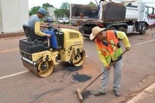 Operários executando o serviço de tapa-buraco. (Foto: Mário Bueno/PMCG)