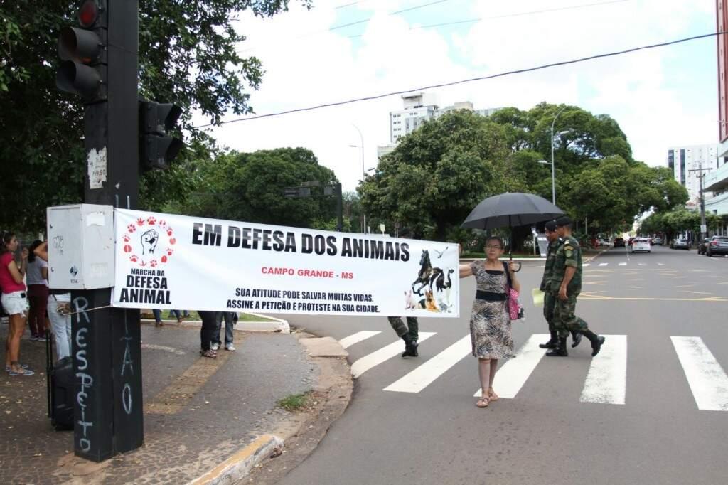 Protetora de animais segurando faixa em protesto na Afonso Pena (Foto: Saul Schramm)