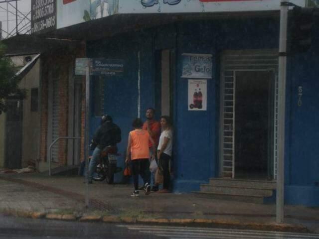 Pedestres e motociclista se protegem da chuva na Rua José Antônio com a Joaquim Murtinho  (Foto: Henrique Kawaminami)