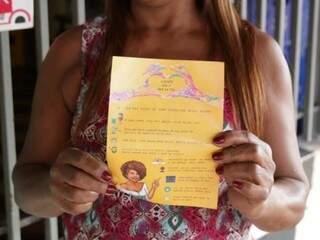Dona do Bar da Tia, Lenir dos Santos Soares segurando panfleto criado por estudantes (Foto: Fernando Antunes)