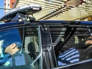 Ex-governador André Puccinelli (PMDB), atrás, no carro da PF saindo de seu apartamento. (Foto: André Bittar/Arquivo).