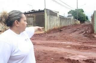 Leila mostra o barro que se formou em frente a casa do sogro e no calçadão, local que os pedestres usavam para caminhar. (Foto: Marcos Ermínio)