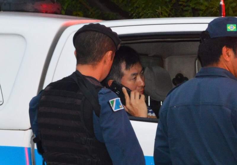 Policial falando ao celular no dia em que matou o empresário com cinco tiros (Foto: Simão Nogueira)