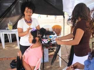 Gislene de blusa branca fazendo a trança Box Braids no cabelo de Ana Fernandes e conta com ajuda de uma participante da oficina (Foto: Marina Pacheco)