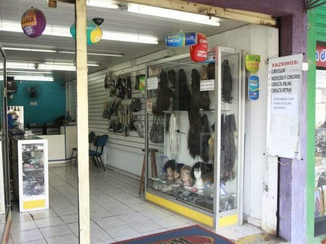 Loja de eletrônicos, com perucas na entrada.