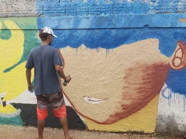 Voluntário grafitando o muro (Foto: Arquivo pessoal)
