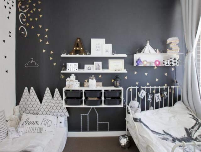 Quarto simples, com o cinza em uma das paredes, branco predominando e adesivos.