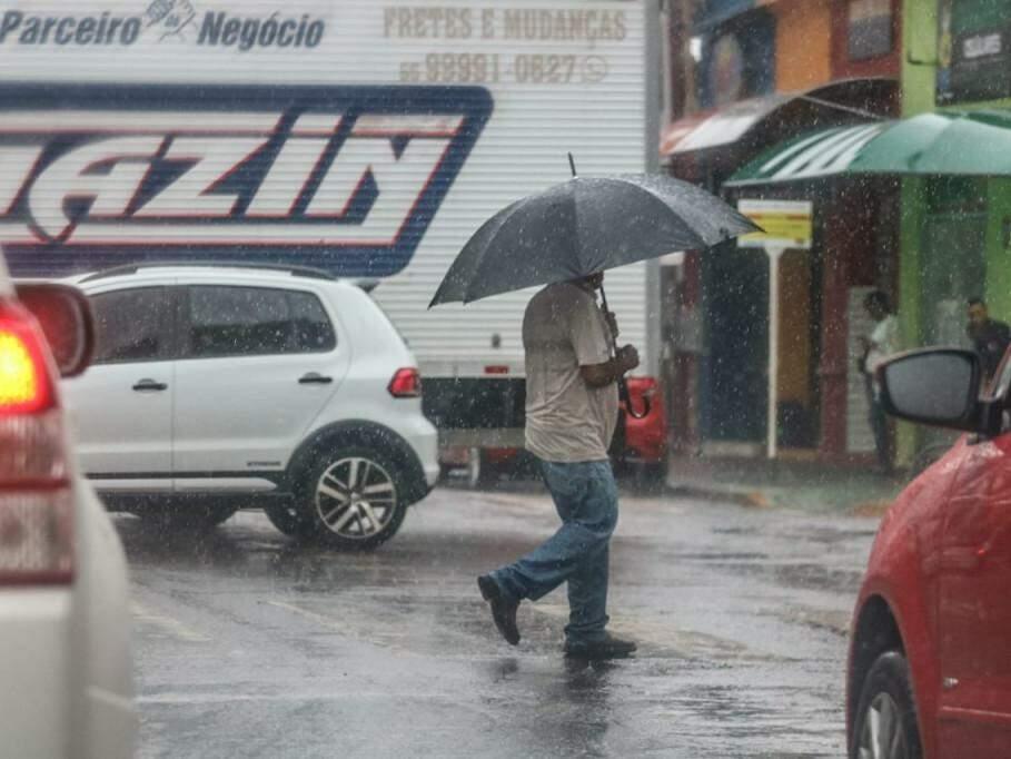 Pedestre estava preparado e abriu guarda-chuva para se proteger de pancada rápida (Foto: Marcos Maluf)