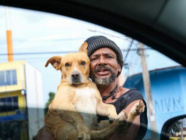 Morador de rua pedindo ajuda segurando seu amigo Amarelinho no colo (Foto: Paulo Francis)