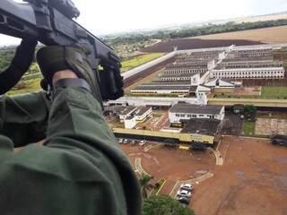 De helicóptero, policial armado observa momento na Penitenciária de Dourados (Foto: Divulgação)
