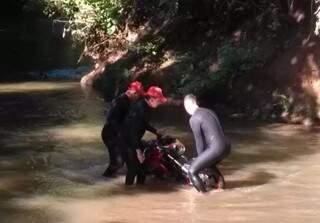 Equipe dos bombeiros retira de córrego moto de vítima jogada no lugar por assassinos. (Foto: Direto das Ruas)
