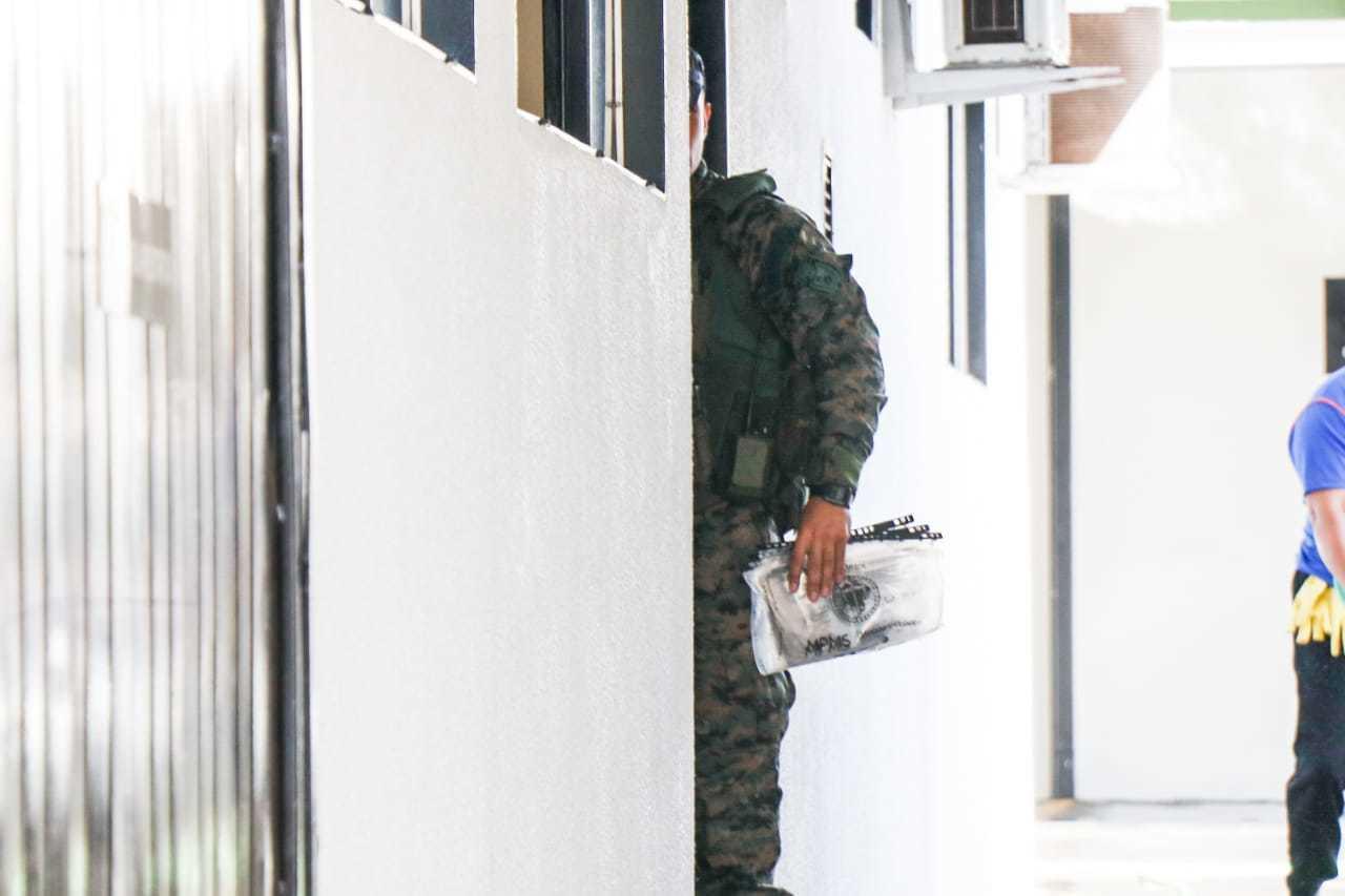Policial entra em delegacia com malote de documentos apreendidos. (Foto: Henrique Kawaminami)