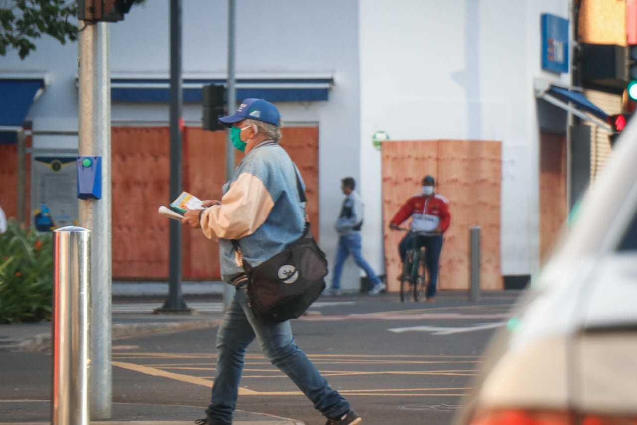 Pedestre caminhando usando máscara de proteção no Centro da cidade. (Foto: Henrique Kawaminami)