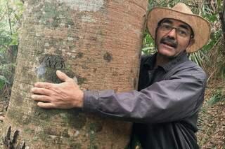 Ruivaldo Nery de Andrade abraçando um tronco durante a gravação do documentário. (Foto: Carolina Freitas da Cunha\Divulgação)