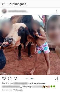 Mulher dá cerveja para vaca enquanto posa para foto tirada por outra, junto com criança. (Foto: Direto das Ruas)