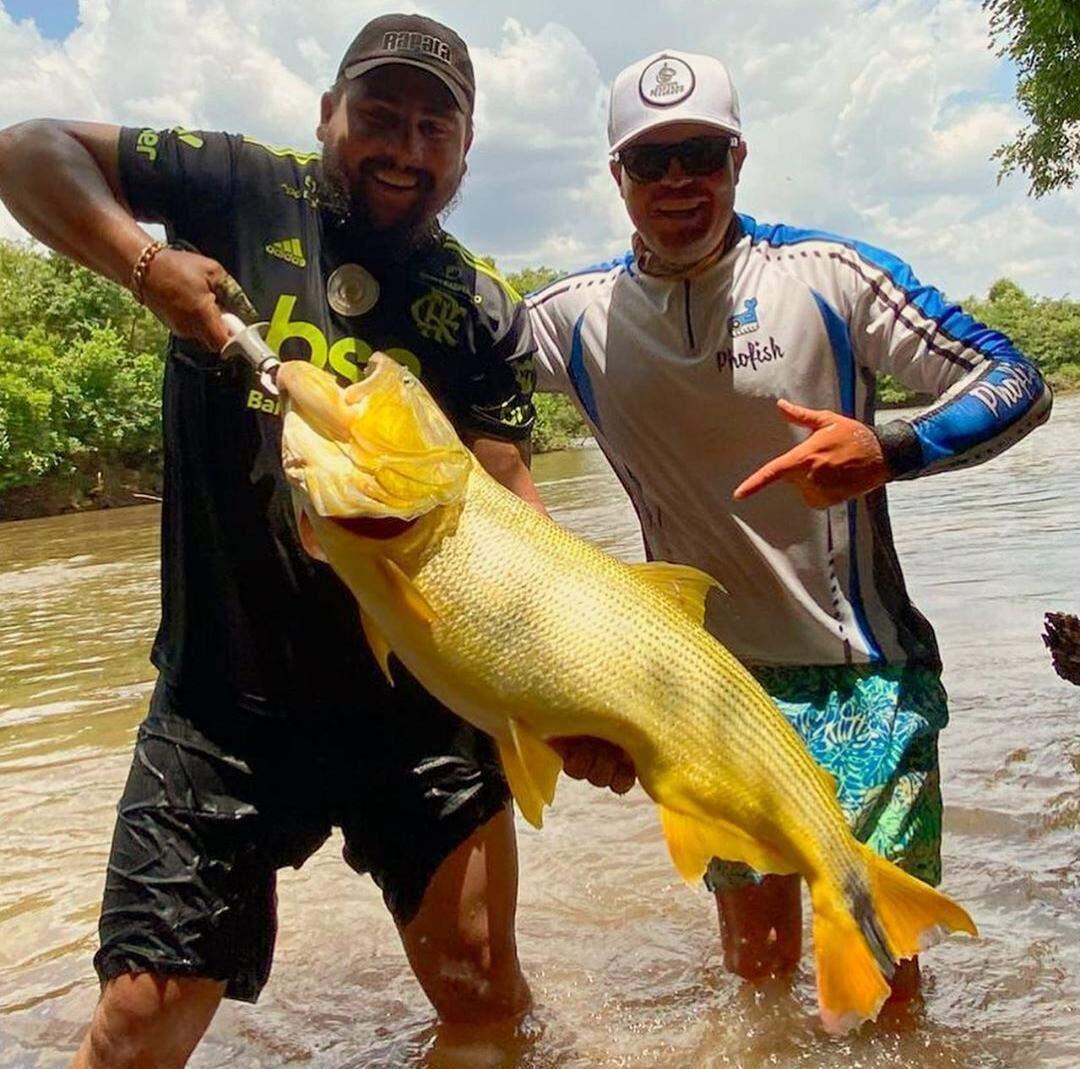Enio segurando o peixão ao lado do amigo e guia de pescaria. (Foto: Arquivo Pessoal)