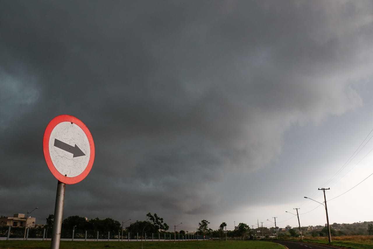 Placa mostra o sentido das nuvens que escureceram a manhã em Campo Grande. (Foto: Henrique Kawaminani)