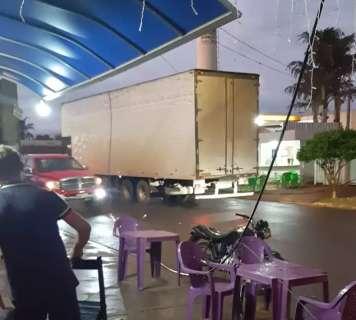 Motorista corta fiação com facão após enroscar caminhão em cruzamento
