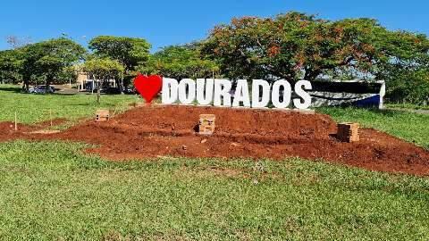 """Com cidade tomada pelo mato, placas exaltam """"amor por Dourados"""""""