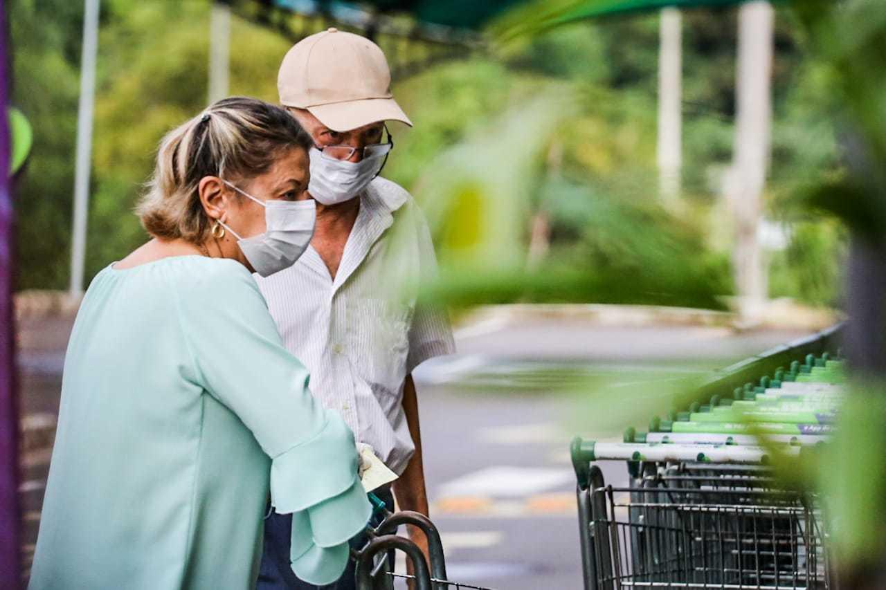 Casal na fila de mercado em Campo Grande; foto foi tirada em março, quando a pandemia fazia os primeiros casos no Estado (Foto: Henrique Kawaminami/Arquivo)