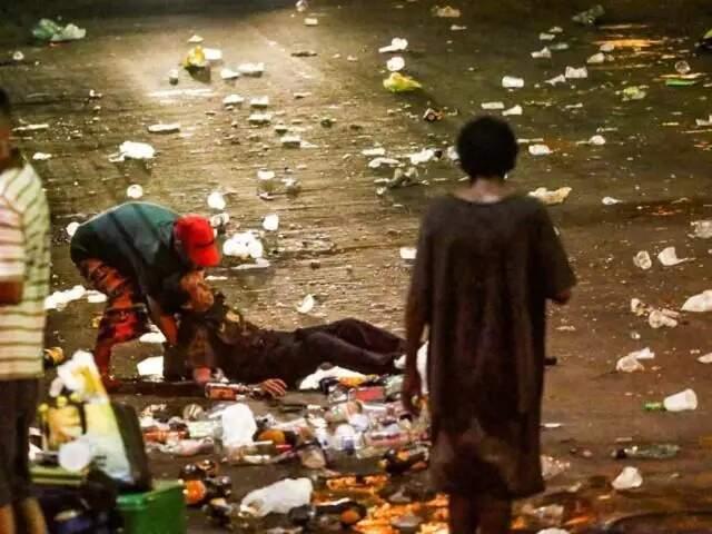 Homem é socorrido por amigo em meio a lixo, em dia de carnaval (Foto: Marcos Maluf / Arquivo)