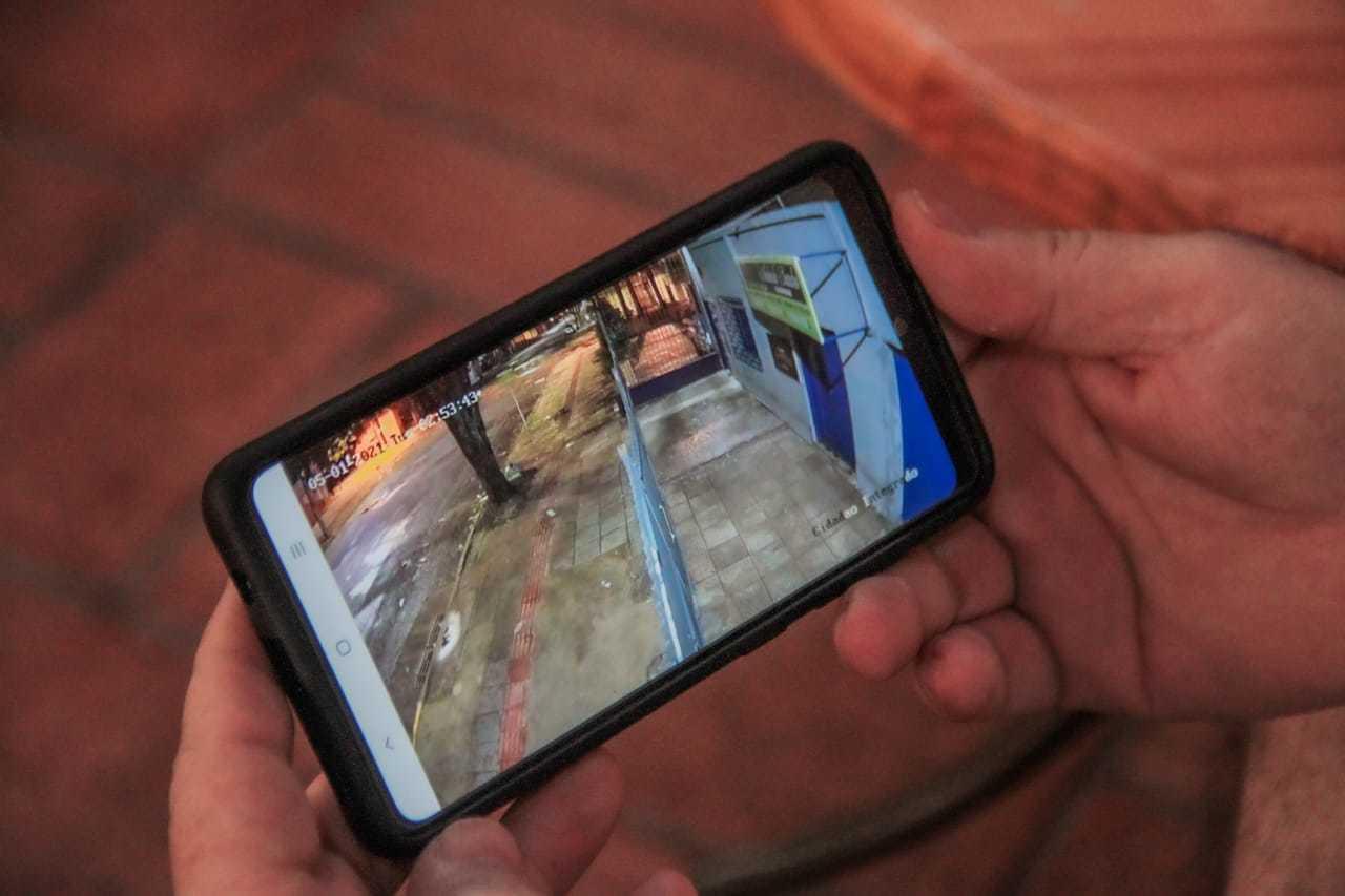 Morador mostra no celular imagens da câmera que vigia ruas. Ele pensa em desistir do Amambaí após 35 anos. (Foto: Marcos Maluf)
