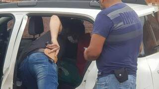 Suspeito, de camiseta polo vermelha, dentro de viatura descaracteriza (Foto: Marcos Rivany)