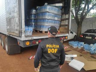 Policial observa caminhão que levava maconha sob garrafas de água mineral (Foto: Adilson Domingos)