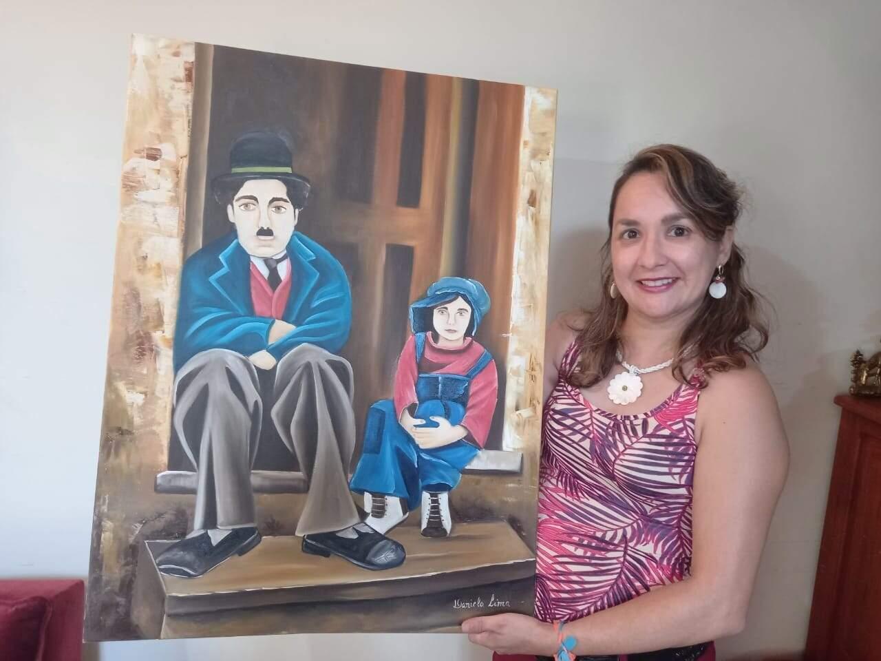 Daniel com retrato de Charlie Chaplin pintado por ela (Foto: Arquivo Pessoal)
