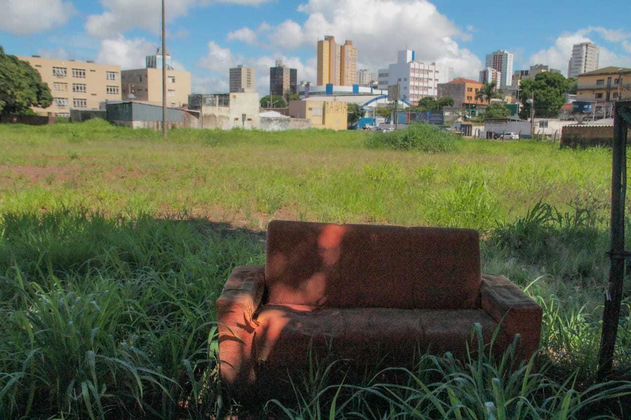 Terreno, que tem até sofá descartado, é um vazio urbano no Centro de Campo Grande. (Foto: Marcos Maluf)