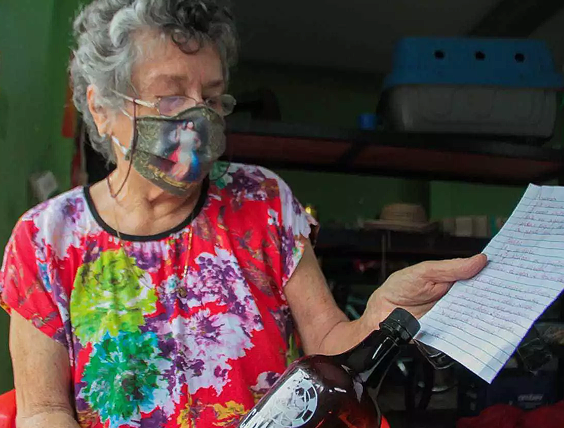 Aqui, mostrando a receita escrita a mão e o frasco de cerveja que utliza no preparo (Foto: Marcos Maluf)