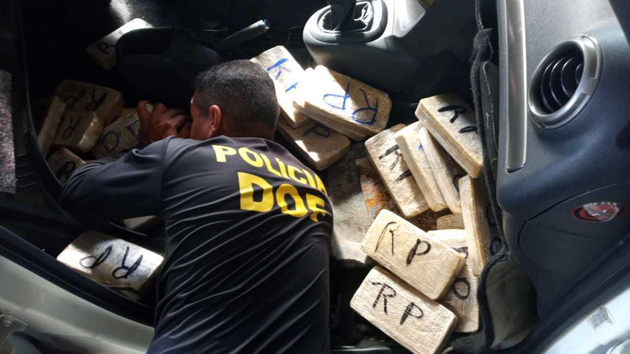 Policial retira tabletes de droga do fundo falso no assoalho de Aircross (Foto: Divulgação)