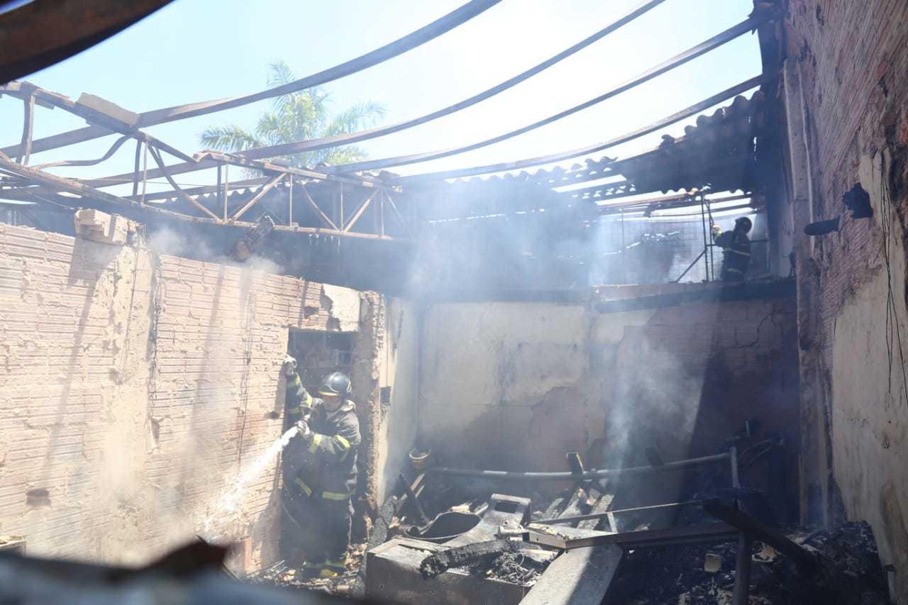 Bombeiro jogando água para conter incêndio dentro da loja de MDF que foi destruida pelas chamas. (Foto: Paulo Francis)