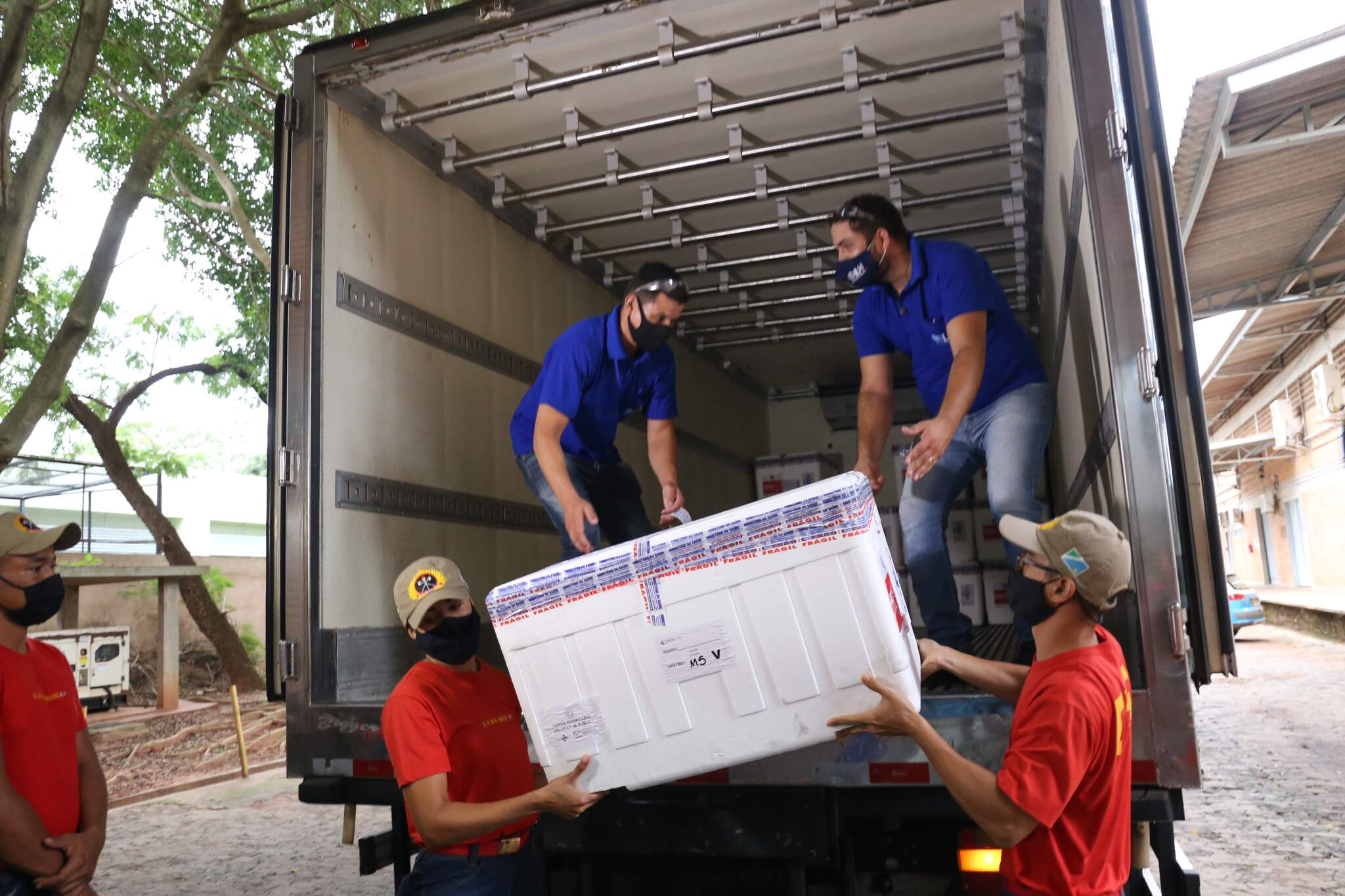 Funcionários carregam caixa com vacinas contra a covid-19, durante a primeira remessa recebida, em janeiro. (Foto: )
