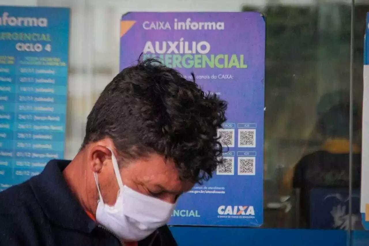 Homem em frente de agência da Caixa, onde parcelas do auxílio puderam ser sacadas; IRPF agora vai cobrar quem recebeu e excedeu teto (Foto: Marcos Maluf/Arquivo)