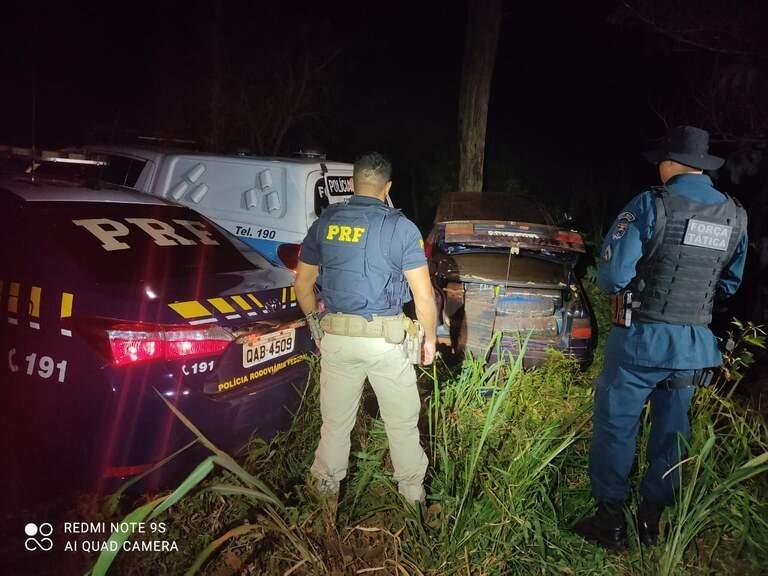 Policiais observam veículo que parou somente após atingir árvore (Foto: Divulgação)