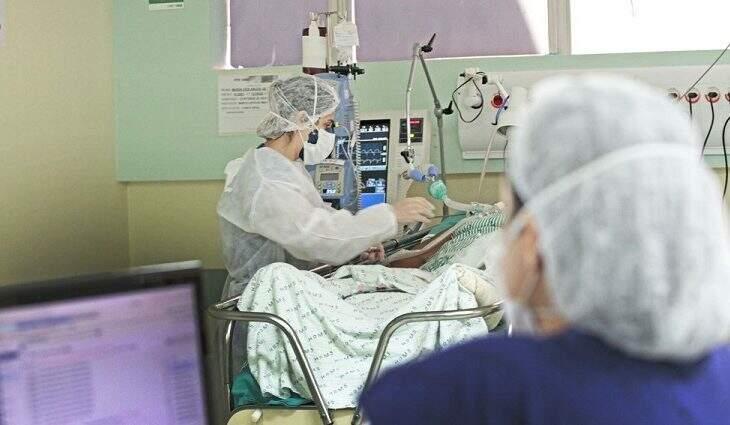 Profissional de saúde atende paciente em leito de UTI. (Foto: Saul Schramm/Governo MS)