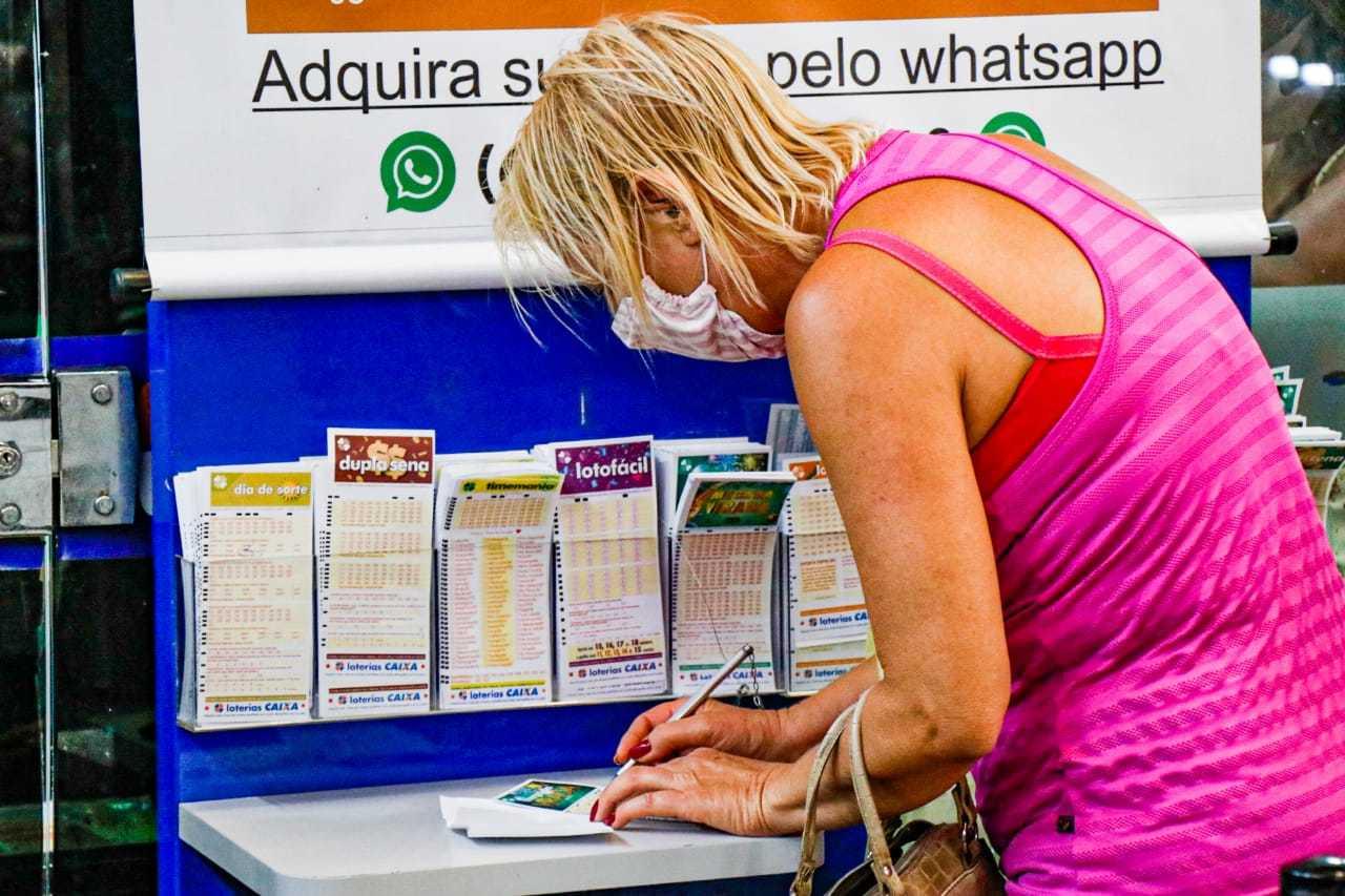 Apostadora preenchendo as dezenas da sorte em uma cartela de apostas. (Foto: Henrique Kawaminami)