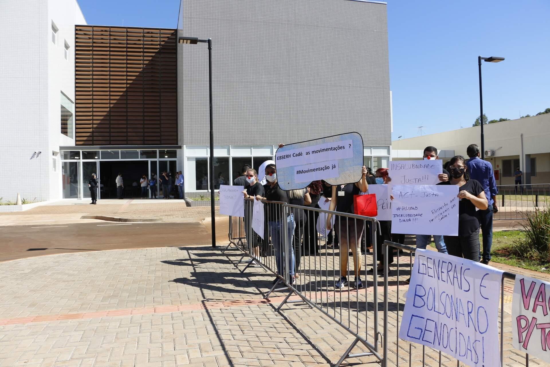 Manifestantes com cartazes em frente à unidade inaugurada hoje (Foto: Helio de Freitas)