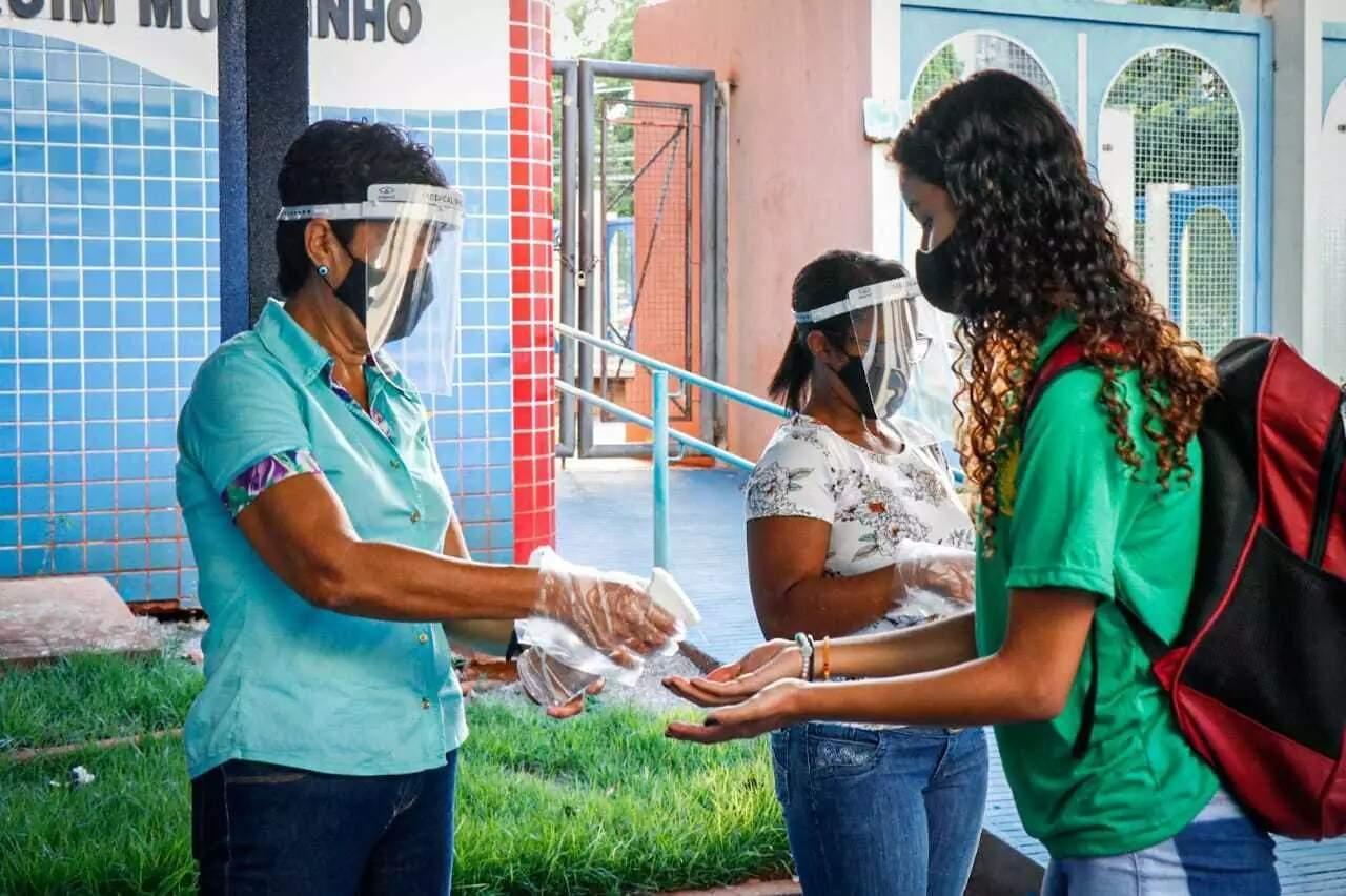 Estudante passando pelos procedimento de biossegurança para entrar em escola (Foto: Henrique Kawaminami/Arquivo)