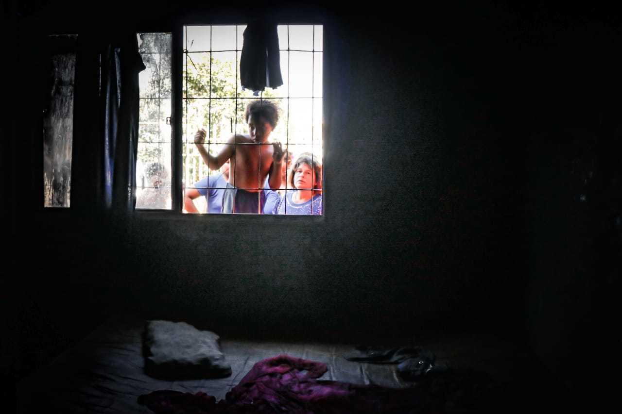 Pela janela, menino olha estragos provocados por incêndio em sua casa. (Foto: Henrique Kawaminami)