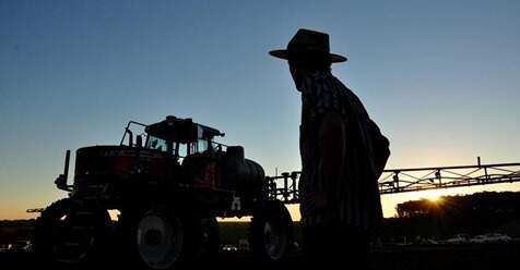 Trabalhador rural de frente para uma máquina usada em lavouras. (Foto: Pìxabay)