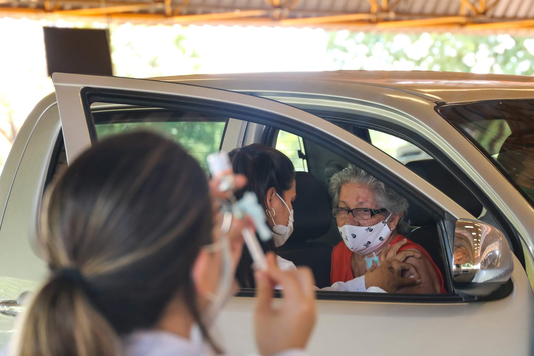 Idosa é vacina no Drive enquanto enfermeira prepara a aplicação de mais uma dose (Foto: Paulo Francis)