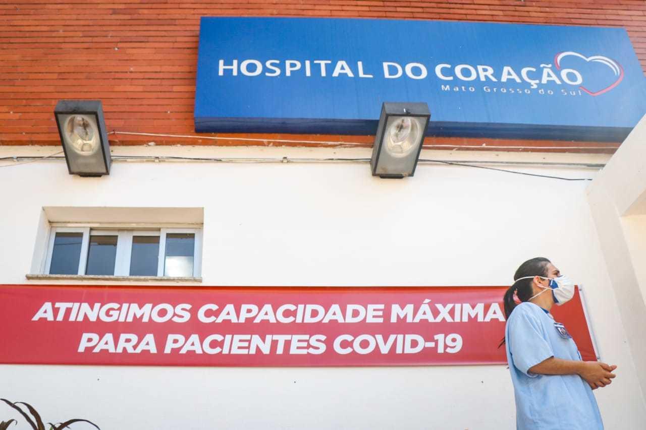 Profissional em frente ao Hospital do Coração, onde faixa indica lotação máxima. (Foto: Henrique Kawaminami)