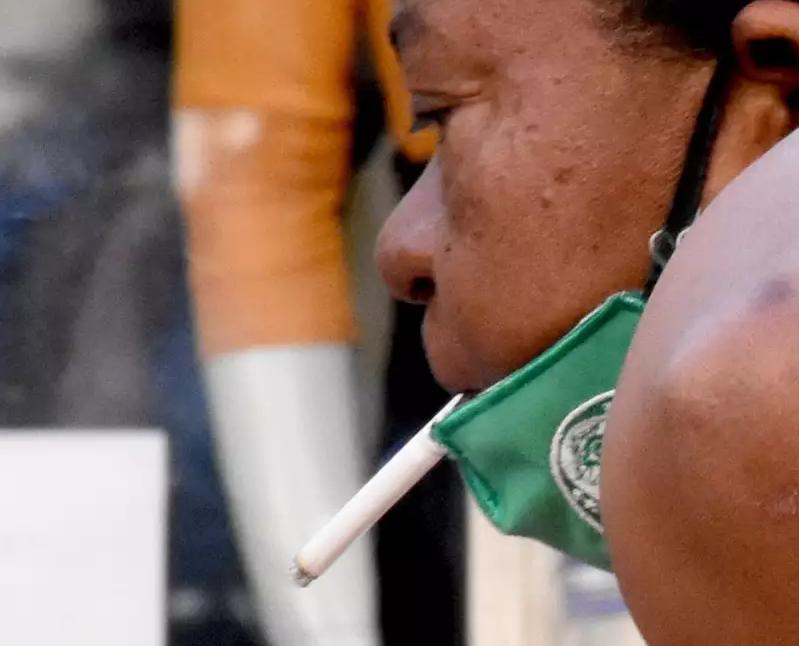 """""""Proteção"""": registro de uma mulher com a máscara abaixada na pausa de furmar um cigarrinho (Foto: Roberto Higa)"""