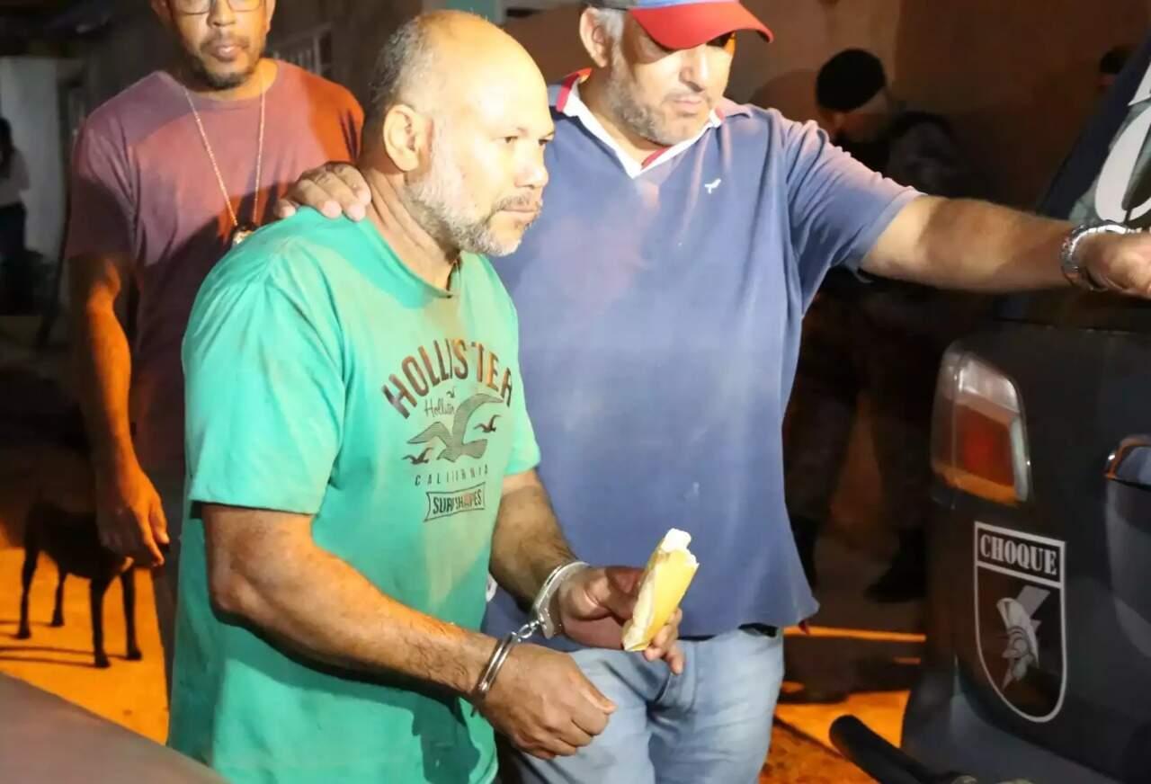 """Cleber de Souza Carvalho, o """"Pedreiro Assassino"""", come pão enquanto é conduzido por policial durante diligências para achar corpos de suas vítimas. (Foto: Kísie Ainoã)"""