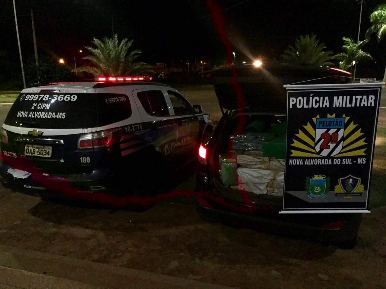 Carro lotado de maconha e skunk ao lado da viatura da polícia (Foto: Divulgação/PM)